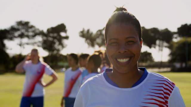 stockvideo's en b-roll-footage met vrouwelijke voetballer staande terwijl teamgenoten praten over voetbalveld. 4k - samen sporten
