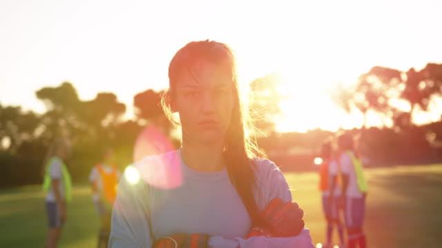 Weiblicher Fußballspieler, der mit gekreuzten Armen auf Fußballplatz steht. 4k – Video