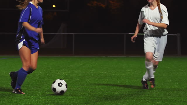 Female soccer players pass the ball during a game at night and make a goal video