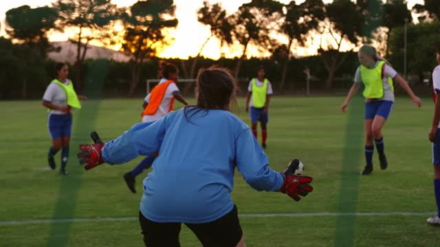 fußballerinnen, die den ball passieren, während die weibliche spielerin fällt. 4k - strafstoß oder strafwurf stock-videos und b-roll-filmmaterial