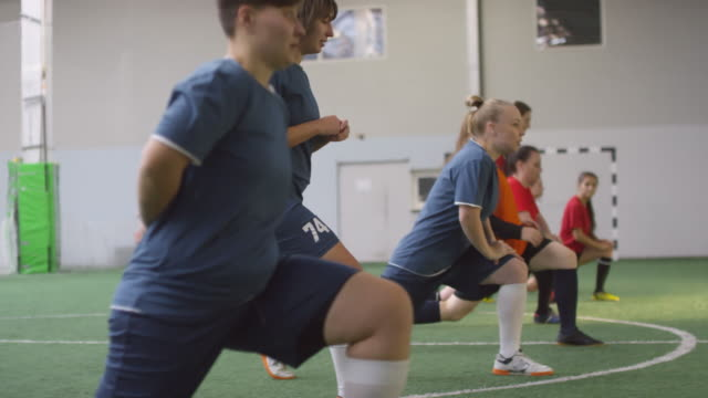 Female Soccer Players Performing Walking Lunges on Field Side view tracking shot of young professional female players in sports uniform performing walking lunges together on field while having soccer pregame workout pre game stock videos & royalty-free footage