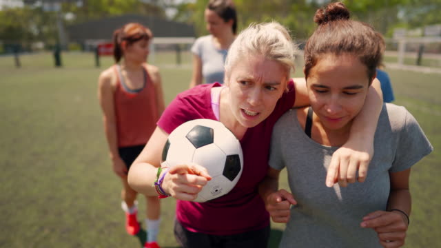 Female soccer players talking about tactics Female friends walking down soccer field, embracing and supporting each other before the game starts pre game stock videos & royalty-free footage