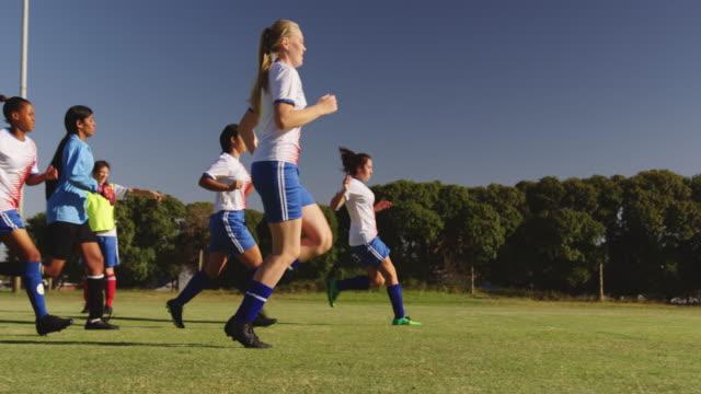 vídeos de stock e filmes b-roll de female soccer team running while team captain gives instructions. 4k - equipamento desportivo