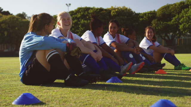 female soccer team sitting on the ground while talking on soccer field. 4k - praticare video stock e b–roll