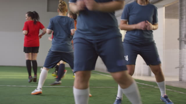 Female Soccer Team Warming Up on Indoor Playing Field Side view tracking shot of professional team of young female athletes in soccer uniform doing sidestep warmup exercise while practicing on indoor sports field pre game stock videos & royalty-free footage