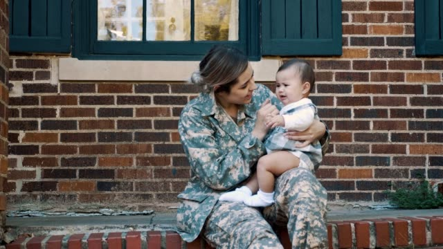 Female soldier comforts her crying baby girl Female soldier sits on the steps outside of her home and comforts her crying baby girl. The woman is preparing to leave for military assignment. porch stock videos & royalty-free footage