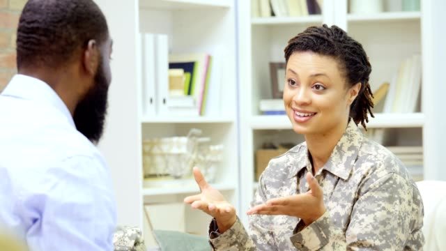 Female soldier smiles while talking with a counselor Beautiful mid adult African American female soldier smiles and gestures while talking to a male African American therapist. The therapist smiles and shakes his head in agreement. military lifestyle stock videos & royalty-free footage