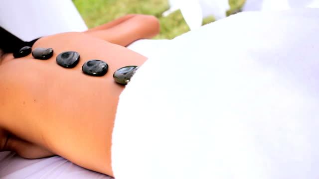 weibliche spa-client entspannend mit hot stone therapie - la stone therapie stock-videos und b-roll-filmmaterial