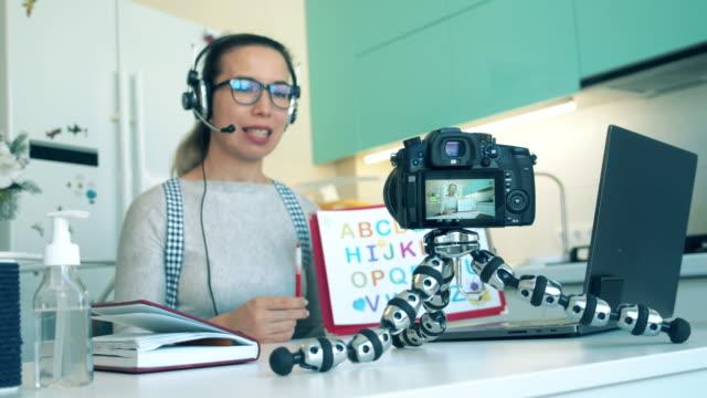 vidéos et rushes de une spécialiste enregistre une vidéo éducative à la maison - enseigner