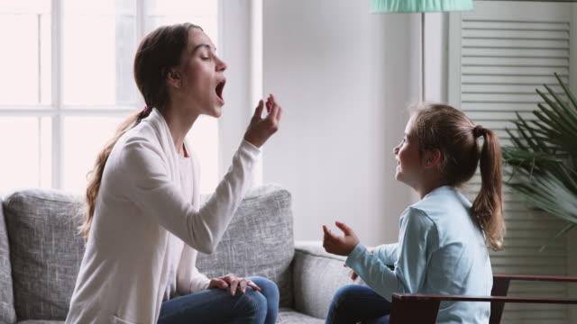 女性の言語療法士は、就学前の子供の女の子を教えるアーティキュレーションを学ぶ - disabilitycollection点の映像素材/bロール