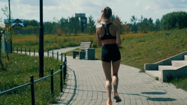vidéos et rushes de sportif féminin faisant du jogging en plein air au stade d'été - joggeuse