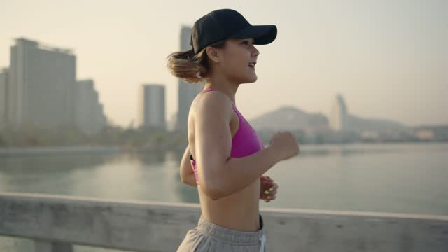 Female sportsman jogging outdoor, using smartwatch during the workout, selective focus in front