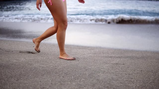 Female sporty legs tourist walking barefoot on shore at sunset. Young woman in pink shorts going along ocean beach and smilling. Girl stepping on wet sand of shoreline. Slow motion video
