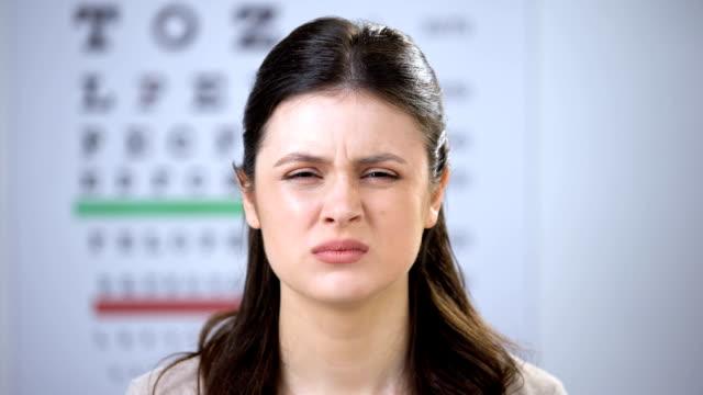 vidéos et rushes de yeux serrants femelles, oculist mettant le réfractaire sur le patient de dame de sourire, lentilles - réfracteur