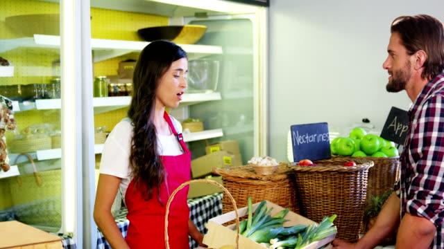 Weibliche Mitarbeiter helfen Menschen bei der Auswahl von frischem Gemüse – Video