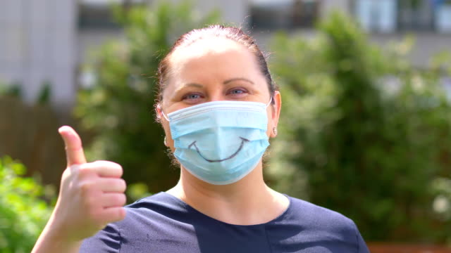 Female standing in Coronavirus mask and showing ok during Pandemic time in 4K Slow motion 60fps video