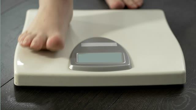 самка наступает на весы, чтобы проверить вес тела, проблемы со здоровьем, ожирение - вес стоковые видео и кадры b-roll