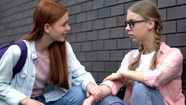 vídeos y material grabado en eventos de stock de estudiante femenina dando ayuda a la chica nerd acosada, amiga de apoyo - stop sign