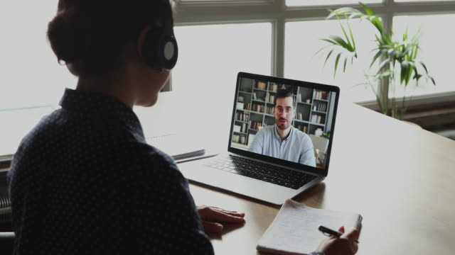 Female student making conference video call talking with teacher