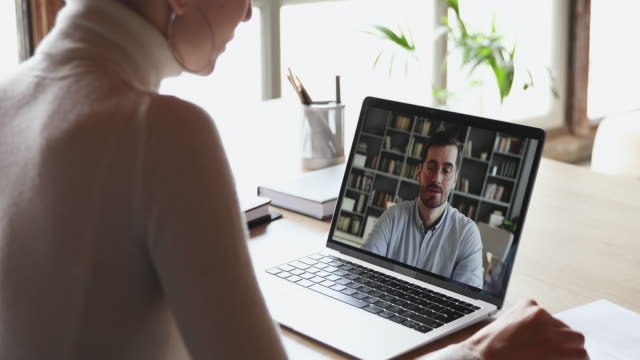 Female student making video call talking with online teacher Over shoulder view of woman student worker makes conference video call on laptop talks with online teacher, boss or partner in web cam chat on computer screen. Distance work, remote education concept. european union currency videos stock videos & royalty-free footage