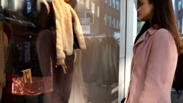 Female student sadly looking at expensive clothes in boutique, window shopping