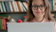 istock Female student sitting against bookshelf and using laptop in the library 1151648216