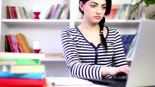 Female student studying at home with a laptop video