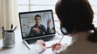 istock Female student wear headphones watching indian teacher webinar training 1223387441