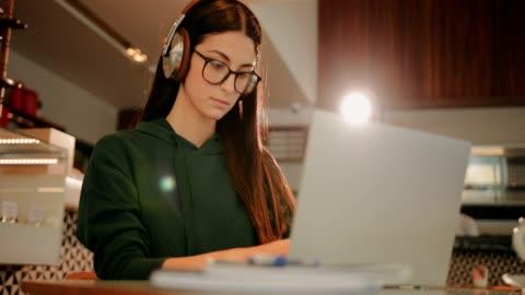 studentessa con laptop e cuffie che fanno i compiti al bar - imparare video stock e b–roll