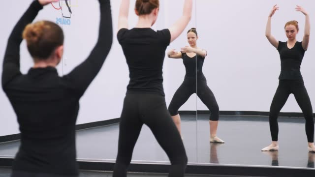 Female Students At Performing Arts School Rehearsing Ballet In Dance Studio Reflected In Mirror Female Students At Performing Arts School Rehearsing Ballet In Dance Studio Reflected In Mirror dance studio stock videos & royalty-free footage