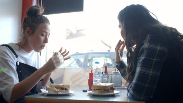 Female Students Eating Sausage Sandwiches In Cafe Together video