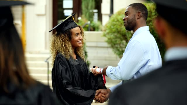Female students receiving college diploma Excited mixed race female college graduate receives a diploma. She shakes hands the the college dean as he hands her the diploma. A young Hispanic female graduate then receives her diploma. university stock videos & royalty-free footage