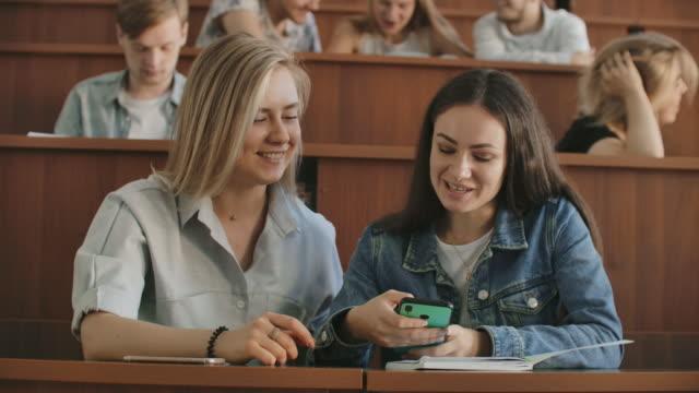 studentinnen mit einem smartphone in der hand lachen im publikum während einer pause für einen vortrag an der universität - vorlesungsfrei stock-videos und b-roll-filmmaterial
