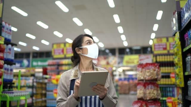 dipendente o proprietario di un supermercato femminile con maschera facciale che cammina e utilizza tablet digitale - vendita al dettaglio video stock e b–roll