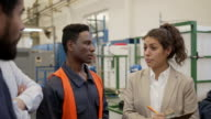 istock Female supervisor discussing something with blue collar workers during a meeting at the factory 1206324499