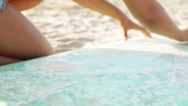 surferin bereitet sich aufs surfen vor - wachs epilation stock-videos und b-roll-filmmaterial