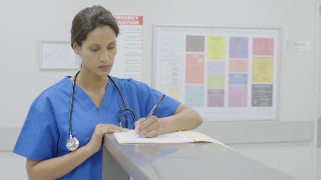 female surgeon filing medical form in hospital - stetoscopio video stock e b–roll