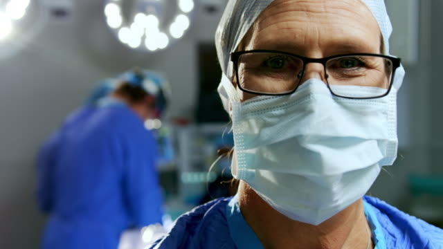 female surgeon standing at hospital 4k - face mask stock videos & royalty-free footage