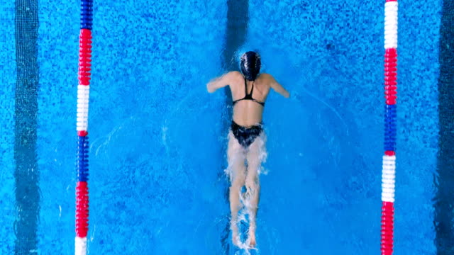 A female swimmer practices a butterfly stroke. A woman swims in a pool using butterfly stroke. swimming stock videos & royalty-free footage