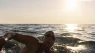 istock SLO MO TS Female swimmer swimming forward crawl in the choppy sea in sunshine 1024302614