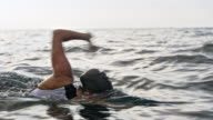 istock TS Female swimmer swimming front crawl in the sea 1030921494
