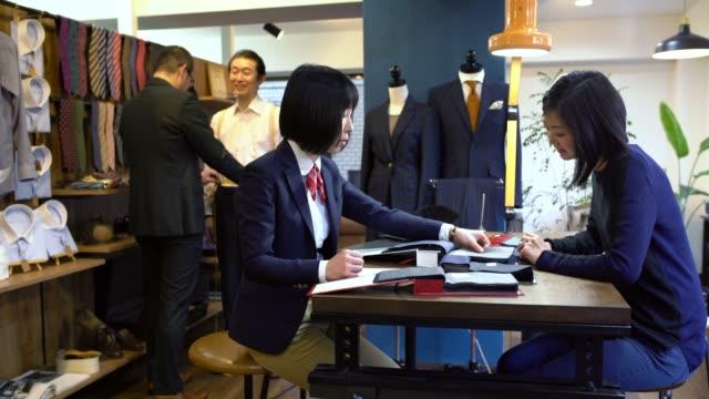 顧客に話している高級スーツ ショップで女性のテーラー - オペレーター 日本人点の映像素材/bロール