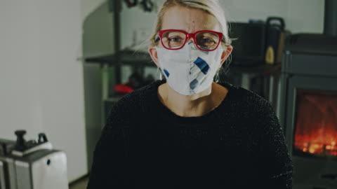 vídeos de stock e filmes b-roll de slo mo female tailor putting on a homemade mask - feito em casa