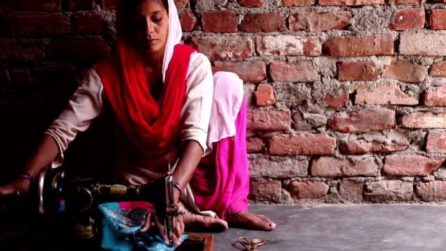 Female tailor, sewing clothes at home using sewing machine video
