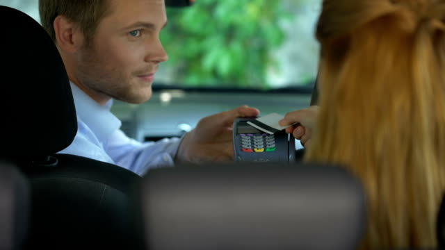 vídeos de stock e filmes b-roll de female taxi passenger paying contactless by credit card terminal, transaction - paying with card contactless