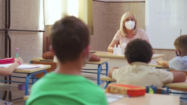 stockvideo's en b-roll-footage met vrouwelijke leraar en schooljonge geitjes met beschermende gezichtsmaskers bij klaslokaal tijdens coronaviruspandemie - lagere schoolleeftijd