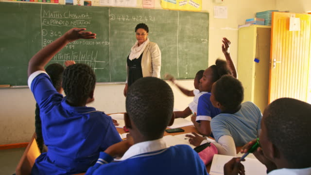 Female teacher and young pupils working in class 4k Front view of a middle aged African female school teacher standing at the front of the class at the blackboard with the rear view of pupils sitting at their desks with hands raised in the foreground then clapping during a lesson in a township elementary school classroom 4k poverty stock videos & royalty-free footage