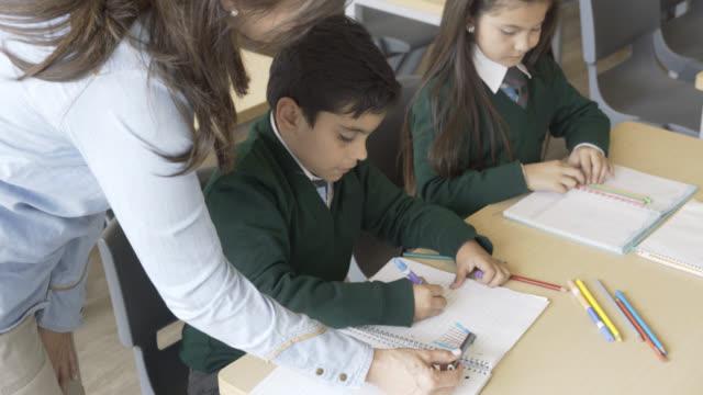 kadın öğretmen onun öğrenci yaptığı çizim hakkında soran - üniforma stok videoları ve detay görüntü çekimi
