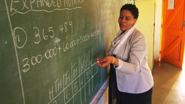 Female teacher at the blackboard in front of class 4k Side view close up of a middle aged African female school teacher standing at the front of the class writing on the blackboard during a maths lesson in a township elementary school classroom 4k blackboard visual aid stock videos & royalty-free footage