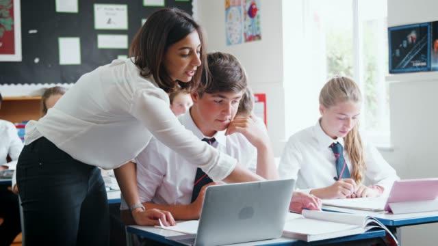 nauczycielka pomagająca uczniowi za pomocą komputera w klasie - uniform filmów i materiałów b-roll